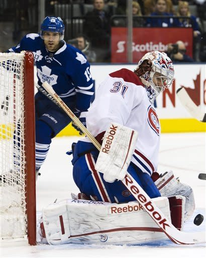 Montreal Canadiens goalie Carey Price, right, eyes the puck after making a save on a Toronto Maple Leafs' shot during the second period of an NHL hockey game, Saturday, Feb. 11, 2012, in Toronto. (AP Photo/The Canadian Press, Nathan Denette)