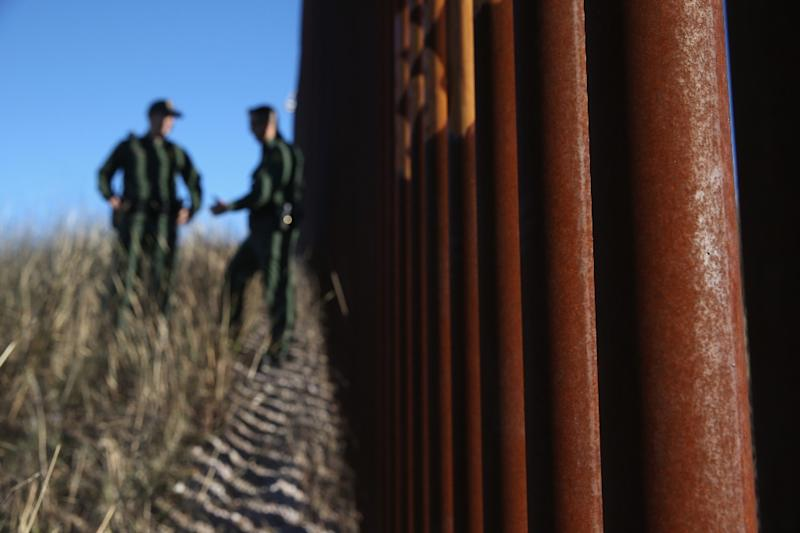 US Border Patrol agents talk next to the US-Mexico border fence on December 9, 2014 near Nogales, Arizona (AFP Photo/John Moore)