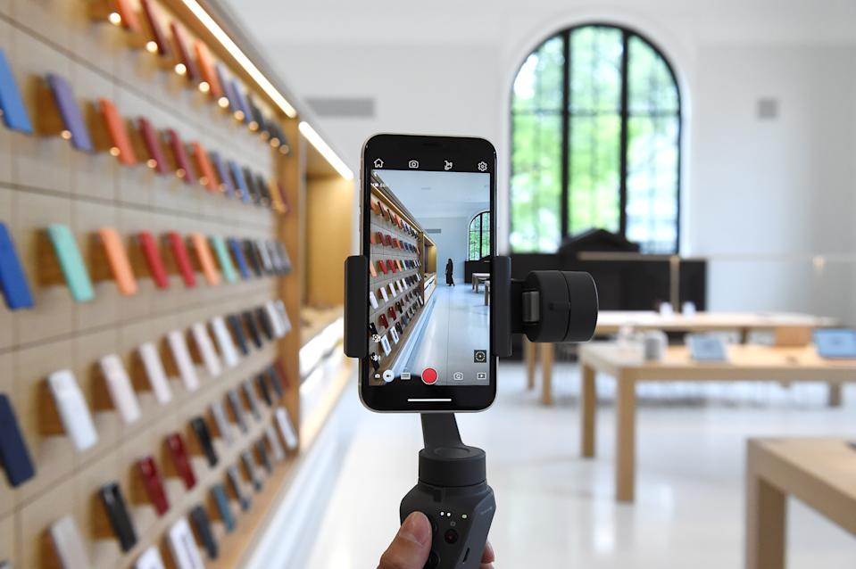 An Apple Store employee demonstrates an iPhone gimbal during the grand opening and media preview of the new Apple Carnegie Library store in Washington, U.S., May 9, 2019. REUTERS/Clodagh Kilcoyne      TPX IMAGES OF THE DAY