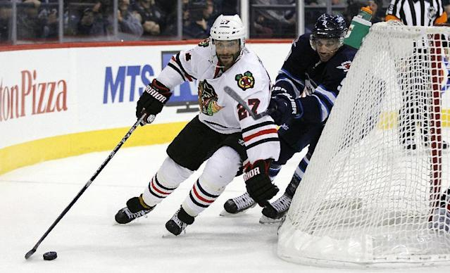 Winnipeg Jets' Evander Kane, right, chases Chicago Blackhawks' Johnny Oduya (27) behind the net during the second period of an NHL hockey game in Winnipeg, Manitoba on Thursday, Nov. 21, 2013. (AP Photo/The Canadian Press, John Woods)