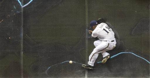 Milwaukee Brewers' Khris Davis cannot make a catch at the wall against the Arizona Diamondbacks during the fourth inning of a baseball game Saturday, April 6, 2013, in Milwaukee. (AP Photo/Tom Lynn)