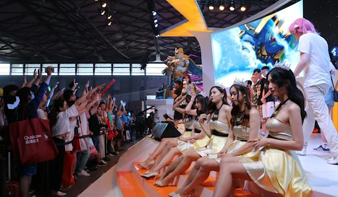 Showgirls interact with audience at the booth of mobile games developer IGG. Photo: SCMP