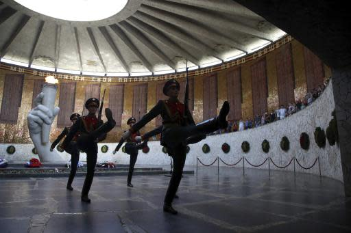 In this Sunday, June 17, 2018 photo, Russian soldiers take part in changing guard at the Hall of Military Glory in Volgograd, Russia. Nearly 60 years since it changed its name to Volgograd, the Russian city once called Stalingrad and its bloody history loom large even in the midst of the fun and football of the World Cup. (AP Photo/Thanassis Stavrakis)
