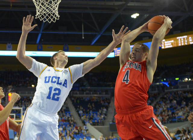 Arizona guard T.J. McConnell, right, grabs a rebound away from UCLA forward David Wear during the first half of an NCAA college basketball game on Thursday, Jan. 9, 2014, in Los Angeles. (AP Photo/Mark J. Terrill)