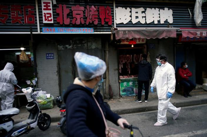 People wearing protective suits is seen at a street market in Wuhan