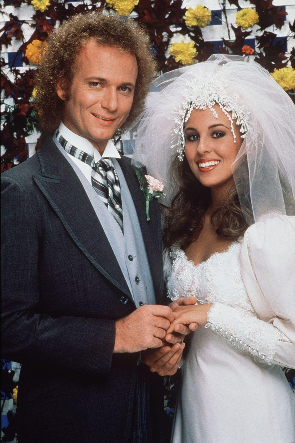 "<p>The <em>General Hospital</em> episode featuring Luke and Laura's ceremony <a href=""https://www.biography.com/news/general-hospital-genie-francis-laura-spencer-interview"" rel=""nofollow noopener"" target=""_blank"" data-ylk=""slk:drew more viewers"" class=""link rapid-noclick-resp"">drew more viewers</a> than Princess Diana's televised wedding to Prince Charles. For a fictional wedding this spectacular, Laura wore an ornate headpiece with lace and tulle veiling, a Victorian era-looking wedding dress with buttoned sleeves, and puffy shoulders – very fitting for the '80s. </p>"