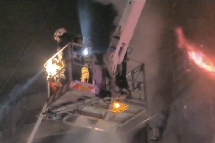 In this image taken from video by Taiwan's EBC, firefighters on a crane fight a fire in Kaohsiung, in southern Taiwan on Thursday, Oct. 14, 2021. The fire engulfed a 13-story building overnight in southern Taiwan, the island's semi-official Central News Agency reported Thursday. (EBC via AP )