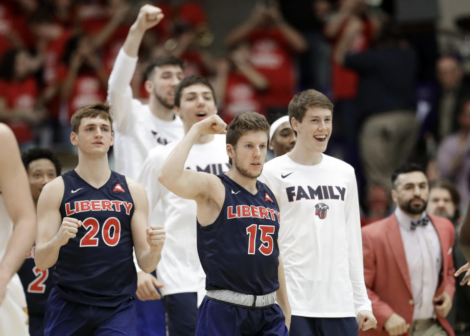 Liberty's Keegan McDowell (20) and Zach Farquhar (15) celebrate a score against Lipscomb in the first half of the Atlantic Sun NCAA college basketball tournament championship game Sunday, March 10, 2019, in Nashville, Tenn. (AP Photo/Mark Humphrey)