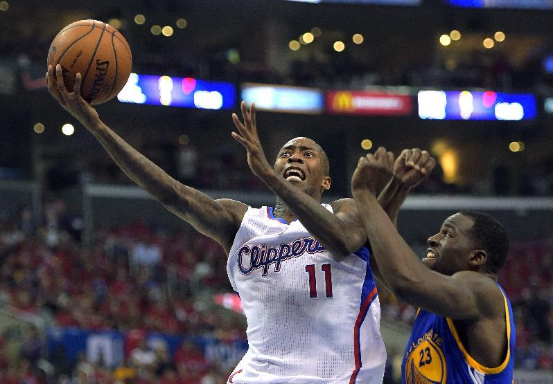 Los Angeles Clippers guard Jamal Crawford, left, goes up for a shot as Golden State Warriors forward Draymond Green defends during the first half in Game 7 of an opening-round NBA basketball playoff series, Saturday, May 3, 2014, in Los Angeles