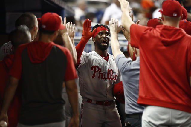 Philadelphia Phillies' Andrew McCutchen (22) celebrates in the dugout after hitting a three-run home run during the eighth inning of the team's baseball game against the Miami Marlins on Friday, April 12, 2019, in Miami. (AP Photo/Brynn Anderson)