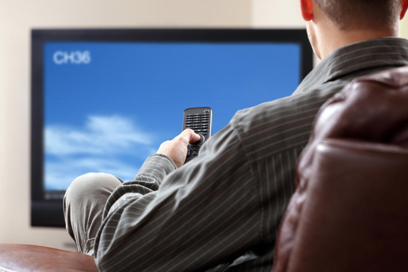 A man watching TV while sitting on a recliner and holding a remote controller