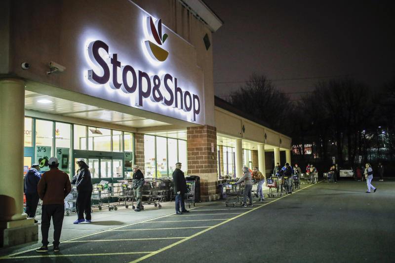 FILE - In this Friday, March 20, 2020 file photo, customers wait in line at a Stop & Shop supermarket that opened special morning hours to serve people 60-years and older due to coronavirus concerns, in Teaneck, N.J. The outbreak of the coronavirus has dealt a shock to the global economy with unprecedented speed as it continues to spread across the world. Stop & Shop will hire at least 5,000 new associates for regular part-time positions in its stores, distribution centers and delivery operations across New York, New Jersey, Connecticut, Massachusetts and Rhode Island.  (AP Photo/John Minchillo, File)