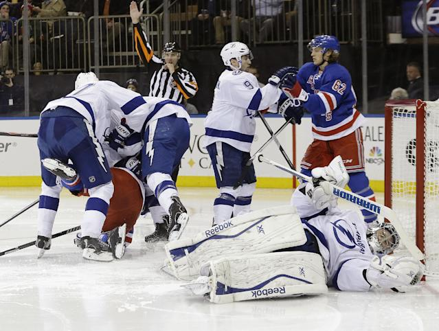 Tampa Bay Lightning's Ben Bishop (30) reacts after being hit with a stick as New York Rangers' Carl Hagelin (62) and Tyler Johnson (9) fight for position during the second period of an NHL hockey game, Tuesday, Jan. 14, 2014, in New York. (AP Photo/Frank Franklin II)