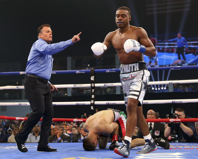 Referee Laurence Cole sends Errol Spence Jr. to a neutral corner after Carlos Camp went down during the first round of a welterweight boxing match Saturday, June 16, 2018, in Frisco, Texas. (AP Photo/Richard W. Rodriguez)