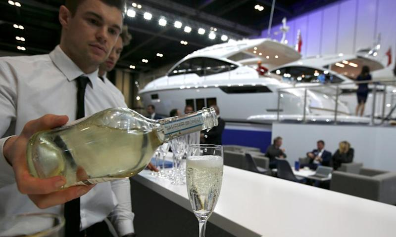 A waiter pours a glass of sparkling wine at a display of luxury yachts, at the London Boat Show