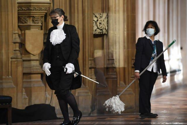 A parliamentary official walks past a cleaner in the Central Lobby