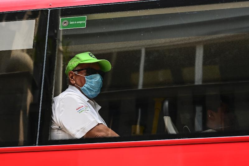 A man on a bus wears a surgical mask to protect against an air pollution spike in Mexico City (AFP Photo/Pedro PARDO)