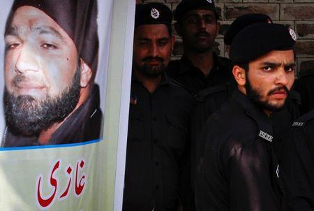 A police officer stands guard next to an image of convicted killer Mumtaz Qadri, outside Adiala Jail where Qadri is being held, in Rawalpindi, October 1, 2011. REUTERS/Faisal Mahmood