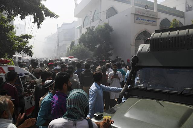 Rescue workers and people gather near the site after a Pakistan International Airlines flight crashed in a residential neighbourhood in Karachi on May 22, 2020. - A Pakistan passenger plane with more than 100 people believed to be on board crashed in the southern city of Karachi on May 22, the country's aviation authority said. (Photo by Asif HASSAN / AFP) (Photo by ASIF HASSAN/AFP via Getty Images)