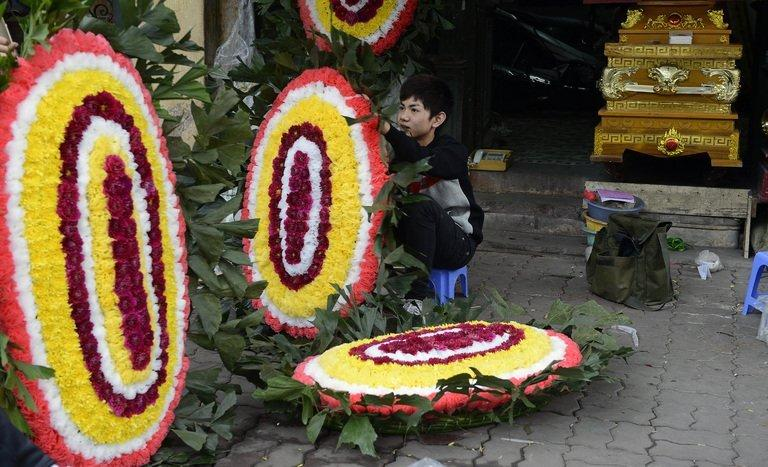 An employee prepares a funeral wreath for a customer in Hanoi on December 21, 2012. For years the country's leaders have leant on war-era nostalgia to shore up authority but now face a modern-day threat -- anger over the economy