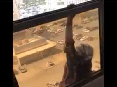The maid is seen hanging from a balcony as her employer looks on and films: Screengrab/Twitter