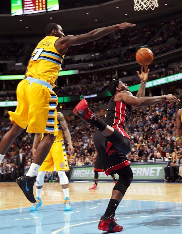 Denver Nuggets forward J.J. Hickson, left, flies in the air to try and block a shot by Miami Heat forward LeBron James in the first quarter of an NBA basketball game in Denver on Monday, Dec. 30, 2013. (AP Photo/David Zalubowski)