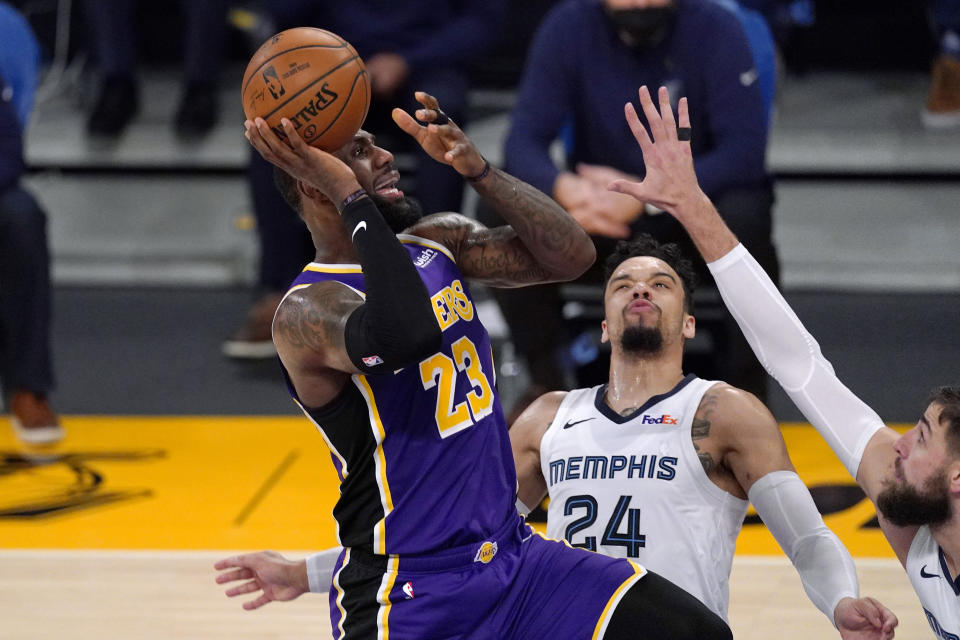Los Angeles Lakers forward LeBron James, left, shoots as Memphis Grizzlies guard Dillon Brooks, center, and center Jonas Valanciunas defend during the first half of an NBA basketball game Friday, Feb. 12, 2021, in Los Angeles. (AP Photo/Mark J. Terrill)