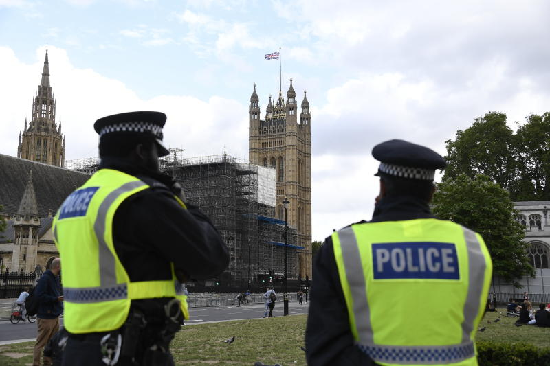 British police officers keep a watchful eye on people at a protest, organised by Black Lives Matter, at the Parliament Square in central London, Sunday, June 21, 2020, in the wake of the killing of George Floyd by police officers in Minneapolis, USA last month that has led to anti-racism protests in many countries calling for an end to racial injustice. Anti-racism demonstrators are holding a fourth weekend of protests across the U.K.(AP Photo/Alberto Pezzali)
