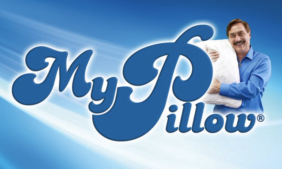 Pictured is Mike Lindell hugging a pillow in a promotional image for his company, My Pillow.