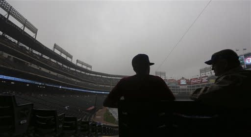 Fans sit in the stands as they wait out a rain delay to the start of the baseball game between the Los Angeles Angels and Texas Rangers Saturday, Sept. 29, 2012, in Arlington, Texas. (AP Photo/LM Otero)