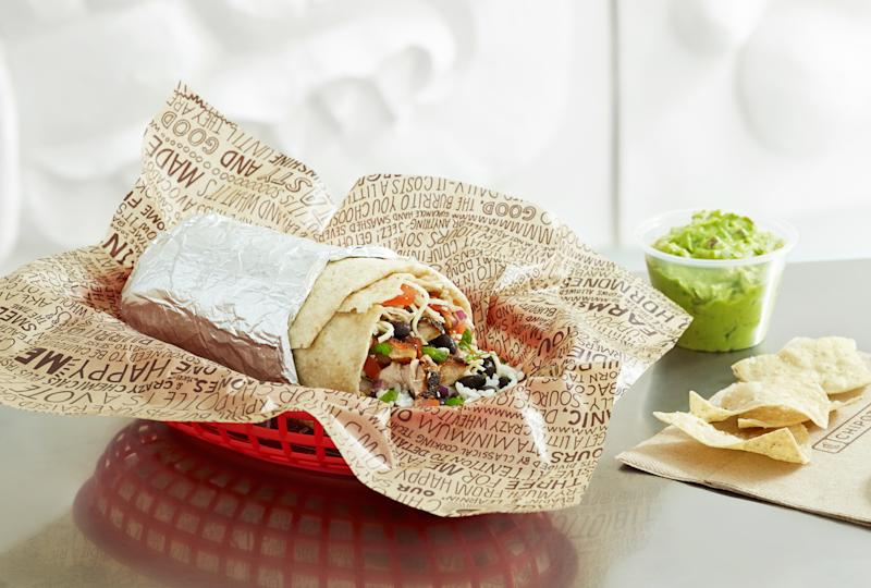 A partially eaten Chipotle burrito with a side of guacamole and chips.