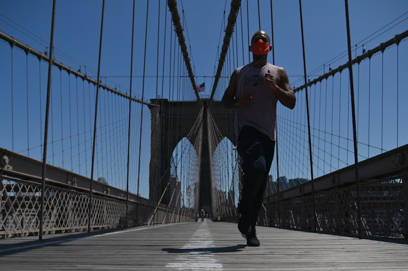A person jogs over the Brooklyn Bridge, amid the novel coronavirus, COVID-19, pandemic, on May 26, 2020 in New York City. (Photo by Angela Weiss / AFP) (Photo by ANGELA WEISS/AFP via Getty Images)