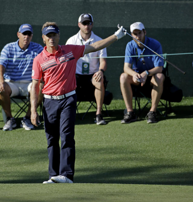 Bernhard Langer, of Germany, holds out his club after his shot to the 15th green during the first round of the Masters golf tournament Thursday, April 10, 2014, in Augusta, Ga. (AP Photo/David J. Phillip)