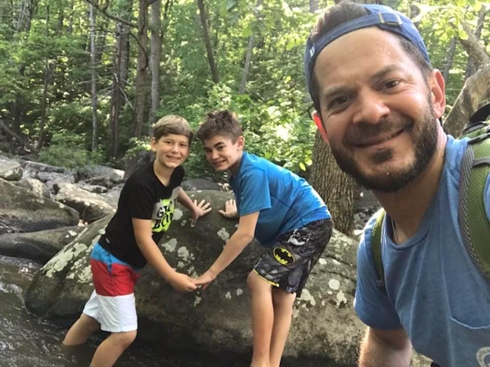 Connor Dobbyn and his brother pose for a photo while hiking with their dad.