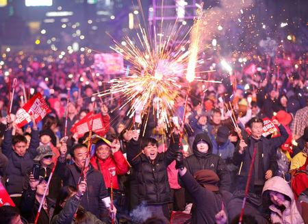 Protesters light fireworks as they celebrate the impeachment of South Korea's ousted leader Park Geun-hye at a rally in Seoul