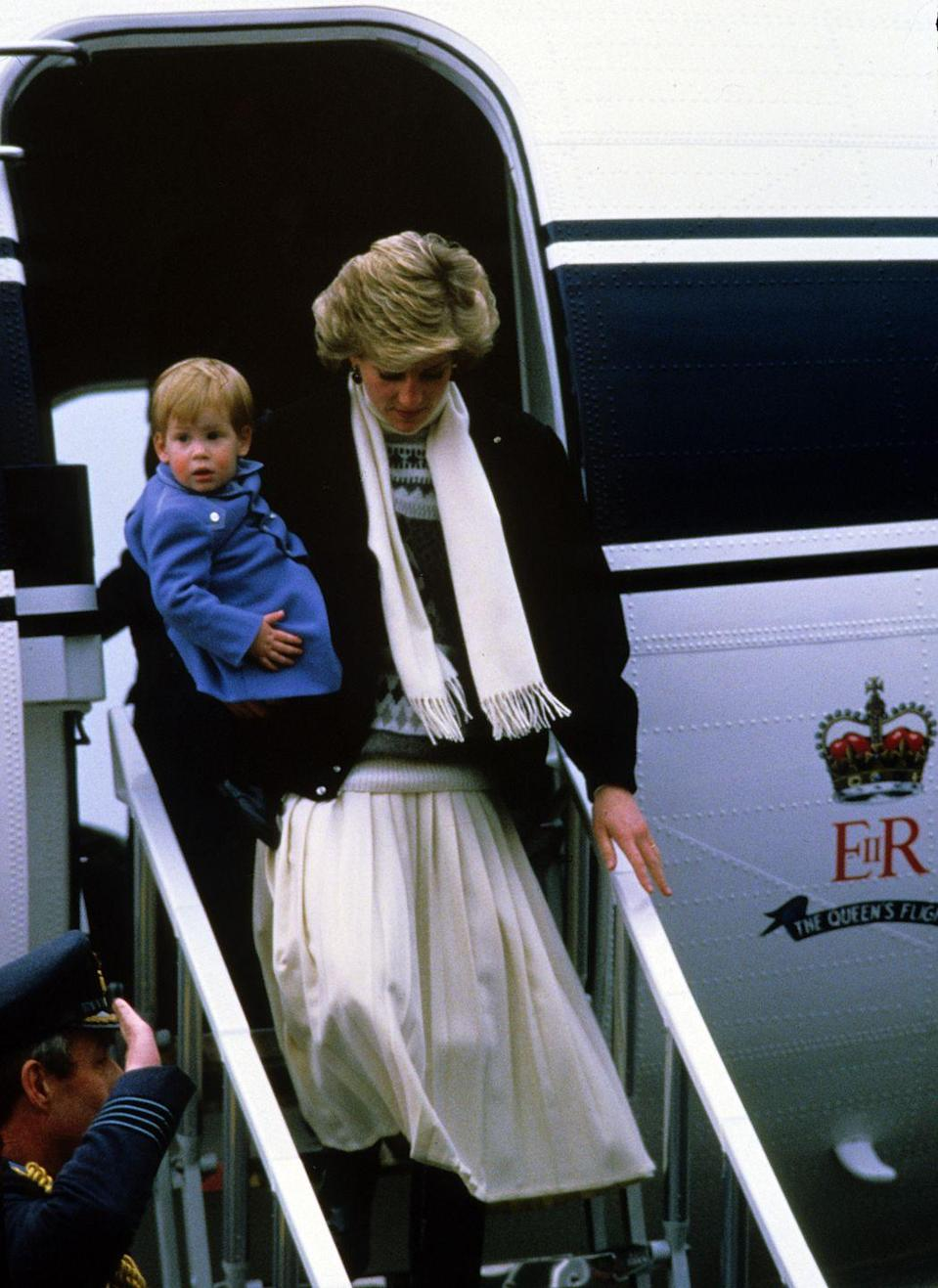 <p>Princess Diana carries a young Prince Harry as they deplane at Aberdeen Airport before heading to Balmoral for a holiday.</p>