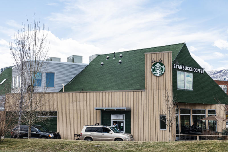 A Starbucks barista hands a drink order out of the drive-thru window in Willits Town Center on Wednesday, April 1, 2020. (Kelsey Brunner/The Aspen Times via AP)