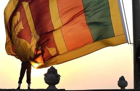 An air force officer holds the Sri Lanka national flag as the sun sets at galle face green in  Colombo
