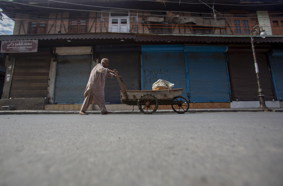 A Kashmiri man pushes a handcart through a closed market in Srinagar, Indian controlled Kashmir, Sunday, Sept. 5, 2021. Authorities Sunday eased some restrictions that had been imposed after the death of top resistance leader Syed Ali Geelani. However, most shops and businesses stayed closed as government forces patrolled roads and streets in the city. (AP Photo/Mukhtar Khan)