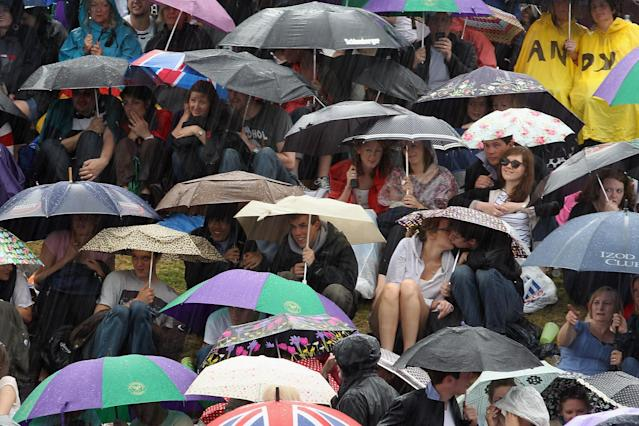 LONDON, ENGLAND - JULY 08: Tennis fans stay in their spots during a torrential rain storm during the third set on 'Murray Mount,' on the final day at Wimbledon, on July 8, 2012 in London, England. Andy Murray is the first British man to reach the finals since 1938, and will take on six time champion Roger Federer. (Photo by Dan Kitwood/Getty Images)