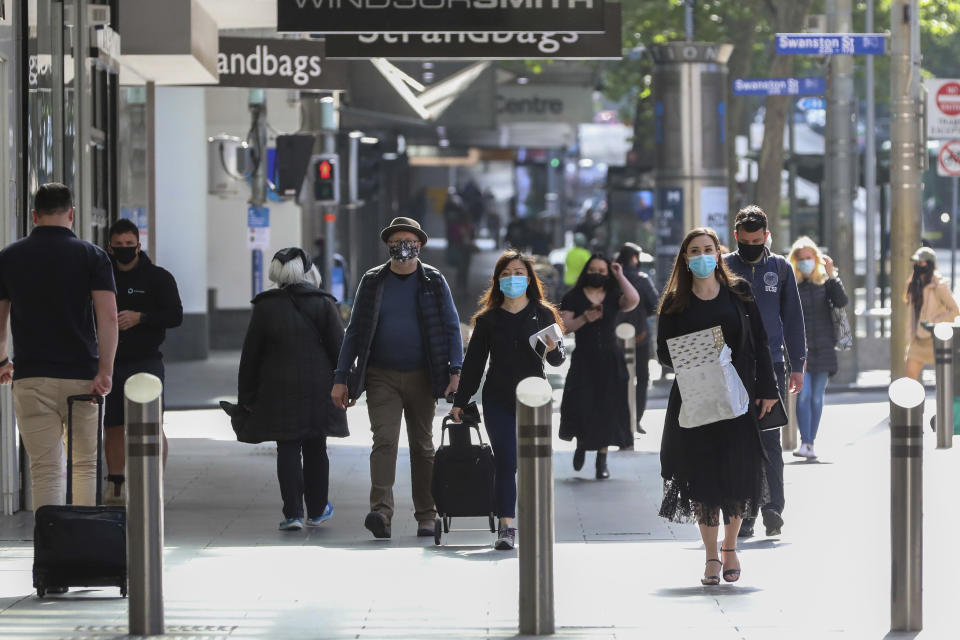 People walk through the Bourke Street Shopping mall in Melbourne, Australia, Wednesday, Oct. 28, 2020. Australia's second largest city of Melbourne which was a coronavirus hotspot emerges from a nearly four-months lockdown, with restaurants, cafes and bars opening and outdoor contact sports resuming on Wednesday. (AP Photo/Asanka Brendon Ratnayake)