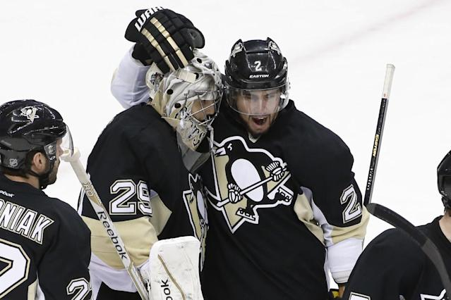 Pittsburgh Penguins defenseman Matt Niskanen (2) celebrates with goalie Marc-Andre Fleury (29) after a 3-1 win over the Columbus Blue Jackets in Game 5 of a first-round NHL playoff hockey series in Pittsburgh, Saturday, April 26, 2014. (AP Photo/Gene J. Puskar)