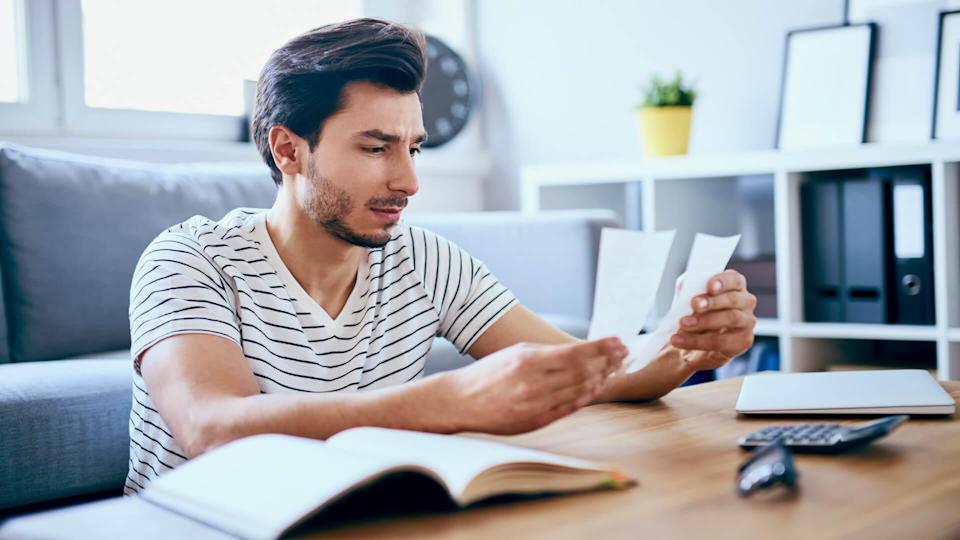 Unhappy man looking at bills sitting at table in living room.