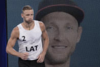 Edgars Tocs, of Latvia, runs past a huge image of himself as he arrives a men's beach volleyball semifinal match against Norway at the 2020 Summer Olympics, Thursday, Aug. 5, 2021, in Tokyo, Japan. (AP Photo/Petros Giannakouris)
