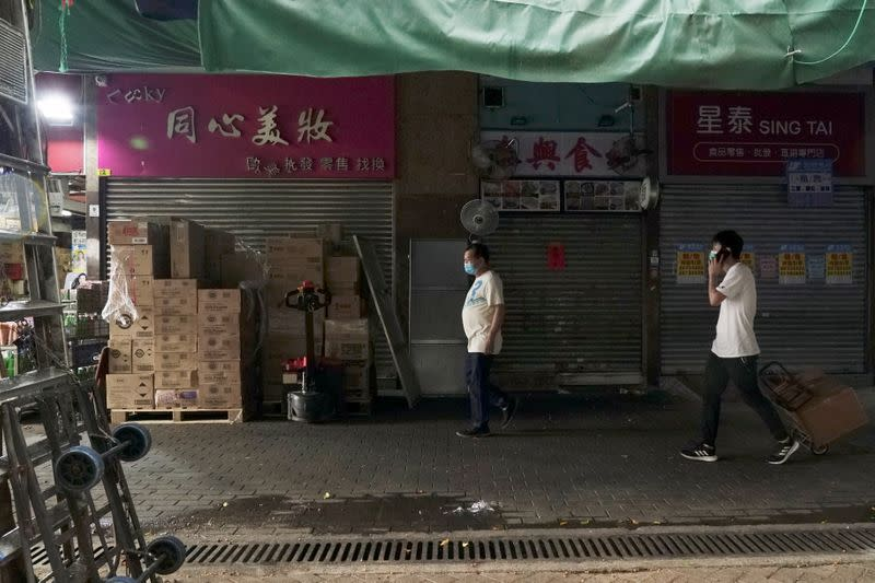 """Men walk past shops catering to """"parallel traders"""" in Sheung Shui"""