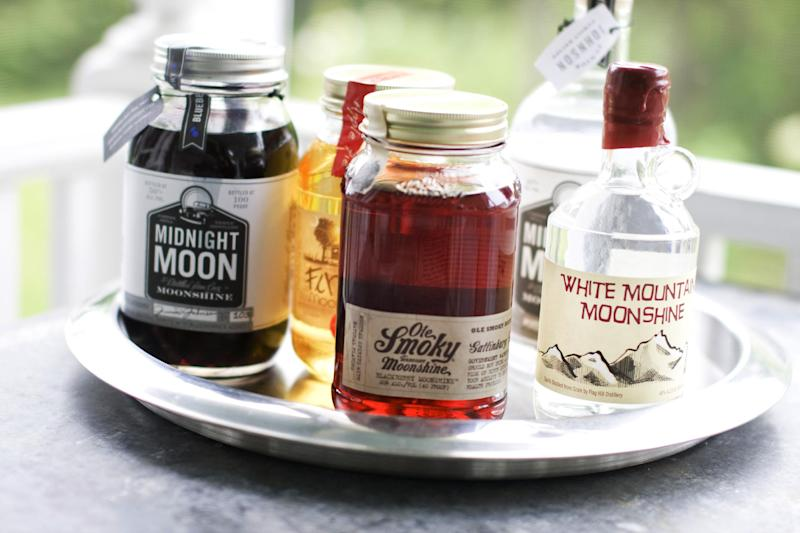In this image taken on June 10, 2013, from left, Midnight Moon Blueberry, FireFly Moonshine Apple Pie Flavor, Ole Smoky Tennessee Moonshine Blackberry, Midnight Moon Moonshine, and White Mountain Moonshine are shown in Concord, N.H. (AP Photo/Matthew Mead)