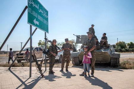 Fighters of the Kurdish People's Protection Units stand with children near a sign in Tel Abyad town