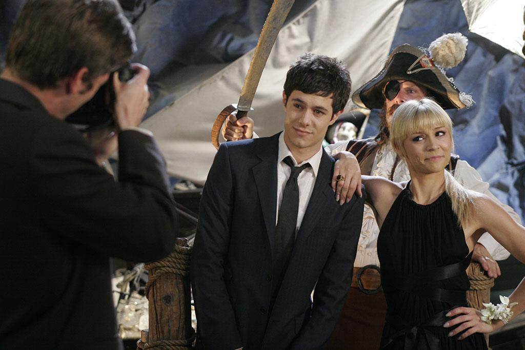 UNSPECIFIED - APRIL 26:  Medium shot at school dance/prom of photographer taking picture of Adam Brody as Seth and Samaire Armstrong as Anna.  (Photo by Greg Gayne/Warner Bros./Getty Images)
