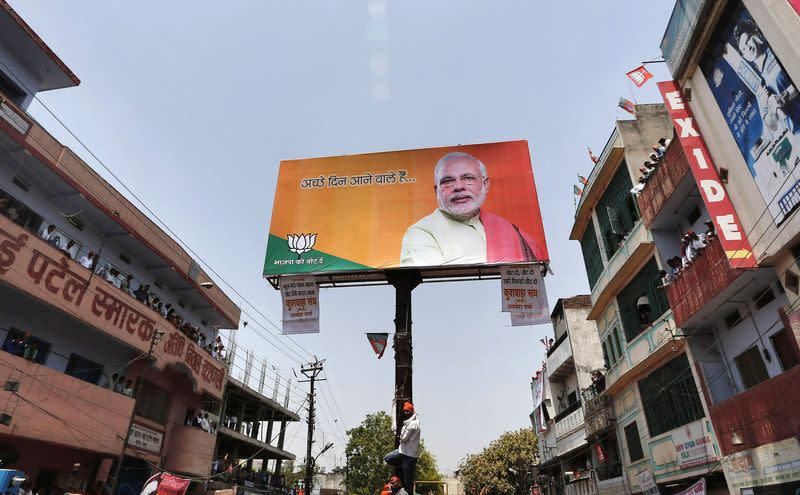 A supporter of Hindu nationalist Modi holds onto a pole installed on a road divider showcasing a picture of Modi in Varanasi