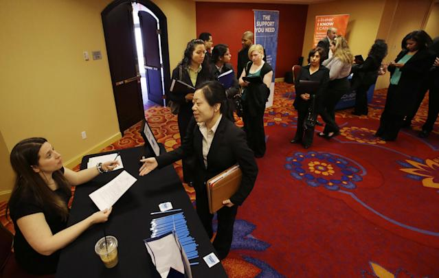 In this Tuesday, Feb. 26, 2013, photo, a line of people wait, as Neely Raffellini, left, helps job seekers revise their resumes during the Edison Career Fair job fair in the Iselin section of Woodbridge Township, N.J. The number of Americans seeking unemployment aid fell 22,000 last week to a seasonally adjusted 344,000, evidence that the job market may be picking up. (AP Photo/Mel Evans)